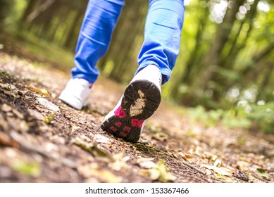 Detail of female running on trail in forest.