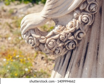 Detail of a female statue of stone, the left back side view, a woman's hand holding a garland of roses, she falls slightly over the swinging skirt part, close-up
