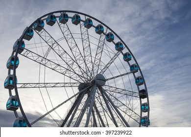 Detail of a ferris wheel against a clouded blue sky