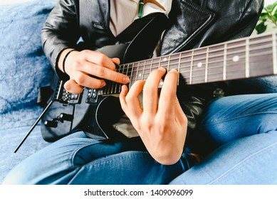 Detail of the fingers of a guitarist placed on the fret of the mast of the guitar playing a chord doing Tapping.