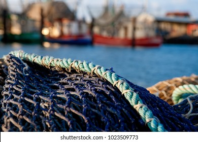 detail of a fishing net in front of (blurred) fishing boats at the coast of the north sea