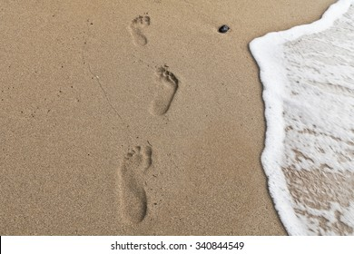 Detail of footprints on the sand and sea