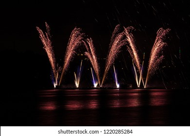 Detail of fountain of gold fire with blue streaks from rich fireworks over Brno's Dam with lake reflection