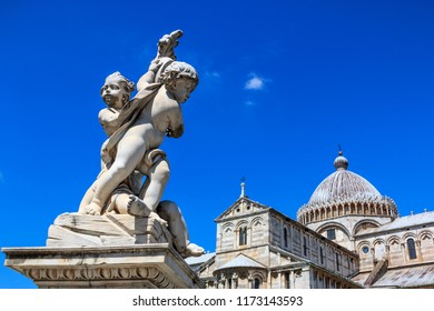 Detail of the Fountain Putti Fountain and the Duomo Santa Maria Assunta at Piazza dei Miracoli square in Pisa, Tuscany, Italy