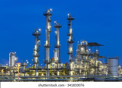 Detail of four distillation towers in a chemical plant and refinery with night blue sky.