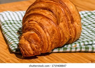 Detail des frischen Croissants auf Holztisch. Das Konzept des Frühstücks. Nahaufnahme des französischen Butterfressers