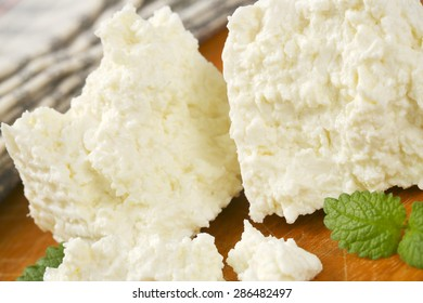 detail of fresh curd cheese slices on wooden cutting board