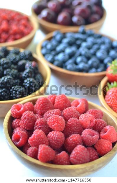 Detail of fresh summer fruit and berries in wooden bowls. Strawberries, raspberries, cherries, blackberries, blueberries and red currants top view.