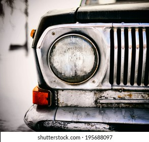 Detail of the front headlight of an old black car. This is dead car, black metal and chrome