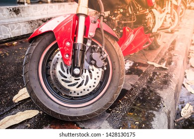 Detail of the front wheel of a red sport motorbike parked on a wet sidewalk with some dead leaves