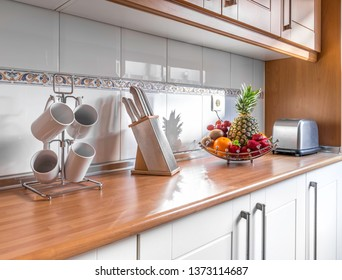 Detail of fruit and kitchenware in a stylish bright kitchen with wooden cabinets. Spacious modern fully equipped appliance interior with wooden desk, ceramic stove and  big windows
