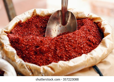 Detail of full bag of spice - red powder of chilly pepper with the spice shovel. Traditional most common Turkish spice.