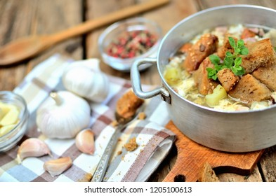 Detail of garlic soup in an old saucepan, fresh garlic bulbs, cloves, colored pepper, wooden spoon, croutons and a towel on a rustic wooden table