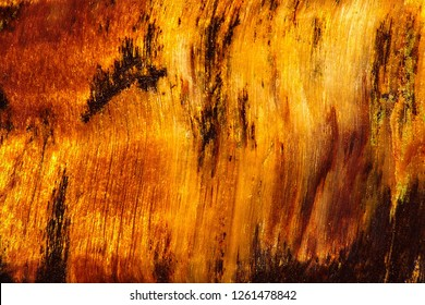Detail of gemstone tiger eye with a golden color contrasted with brown. Tiger eye texture as nice mineral background. Mineral quartz beautiful golden-brown color with a silky sheen.