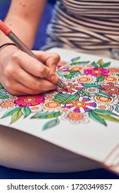 Detail of a girl coloring a flower mandala with a red marker