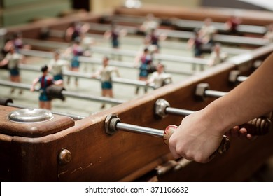Detail of girl's hands playing the foosball vintage table match. Color toned image. Concept photo of leading the company.