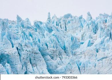 Detail of a glacier; blue of dense ice (melting and subliming ice) in Alaska, Aialik Glacier, which is a glacier in the Kenai Peninsula Borough of Alaska (Kenai Fjords National Park)