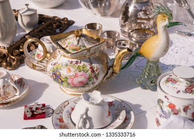 detail of glass bird and vintage tea pot among china cups on sale at street market, shot in bright winter light at Cremona, Lombardy,  Italy
