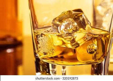 detail of glass of whiskey with ices near bottle on table with reflection, warm atmosphere, time of relax with whisky