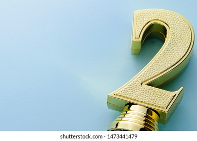 Detail of a gold second place winners trophy in the form of a dimensional metallic number two on a blue studio background with copy space