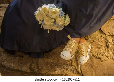 Detail of golden tennis shoes, elegant blue dress and a flower arrangement of white roses, fifteen year party concept, fifteen years