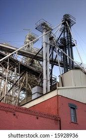 detail of grain elevator with gravity flow pipes and red brick main building