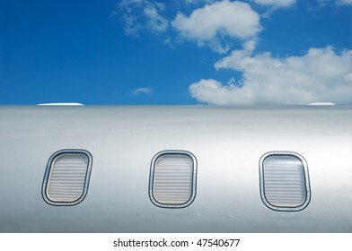 Detail of gray metallic corporate jet with windows closed by blinds.