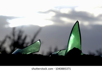 Detail of green pieces of glass on a wall with a sunlight sky background