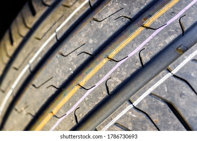 Detail of the grooves of a new car tire.