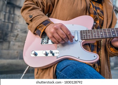 A detail of a guitar player busking on his guitar