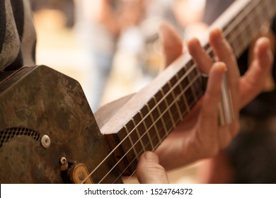 Detail of guitar player playing slide bottleneck on a cigar box guitar.