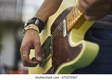 Detail of a Guitarist who plays his electric guitar at a live rock music concert.