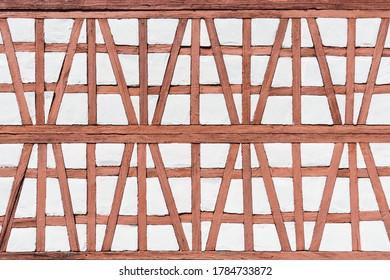 Detail einer halb bebauten Fassade eines alten, hellbraunen, roten, weißen Modellbauhauses