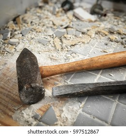 Detail of a hammer and chisel used to remove old bathroom ceramic tile.