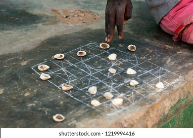 Detail of the hand of a boy playing a game with shells at the village of Eticoga in the island of Orango in Guinea Bissau, West Africa