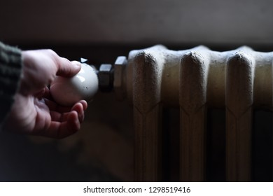 Detail with a hand checking the heat coming from a household radiator