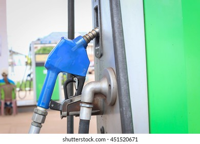 Detail of a hand holding a fuel pump at a station