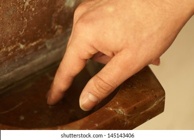Detail of hand and holy water stoup in the church.
