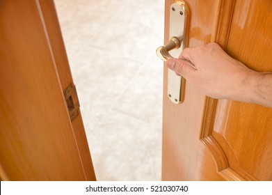 detail of hand opening the wooden door