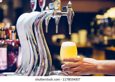 Detail of the hand of a waiter is serving a cold glass of beer near a beer tap on a counter bar
