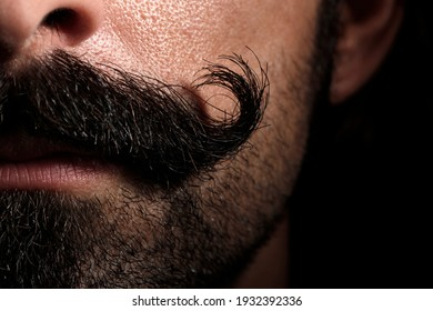 """Detail of a """"handlebar"""" mustache of a white man"""