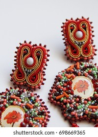 Detail of handmade red earrings on white background