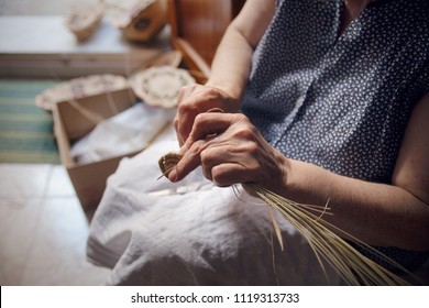 Detail of the hands of an elderly lady who is Weaving a basket in Castelsardo, traditional handicraft of the famous medieval town in the north of Sardinia island, Italy, Europe.