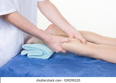 Detail of hands massaging human calf muscle.Therapist applying pressure on female leg.