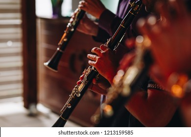 detail of hands playing clarinet instrument