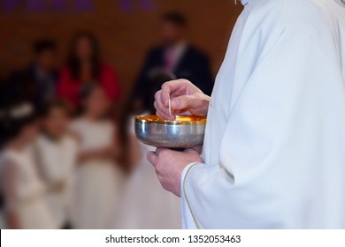 detail of the hands of a priest at the time of giving the first communion to children. You can see the cup of the count that is the bread that twists the body of Christ.