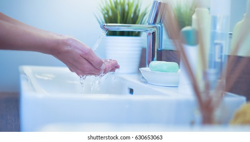 Detail of the  hands of a young woman washing her face with clean water in bathroom