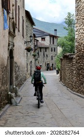 Detail of healthy woman riding her bike through the stone houses and woods of Anciles, a village nearby Benasque, one of the most amazing spots of the Spanish Pyrenees mountains.