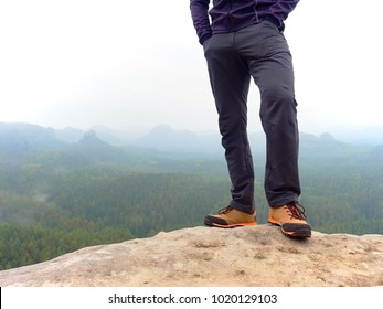Detail of  hiker legs in black orange hiking boots on mountain summit. Feets in trekking shoes and legs  light trousers  on background of the peaks