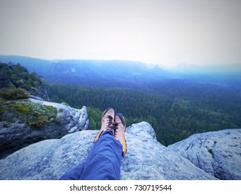 Detail of  hiker legs in black orange hiking boots on mountain summit. Feet in trekking shoes and legs  light trousers  on background of the peaks